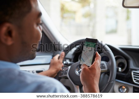 In car view of young male African American looking at maps app on his phone