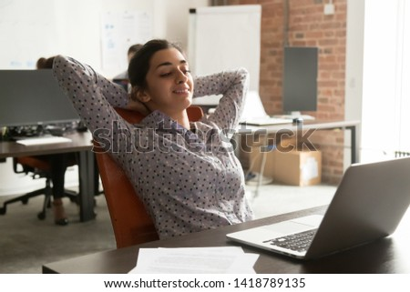 In coworking room worker indian ethnicity girl leaning on office chair put hands behind head look at pc screen read media news take break complete work relaxing. No stress end of working day concept
