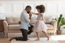 In cozy living room african dad got down on one knee kisses hand of daughter princess wearing fluffy pink skirt, chivalrous gesture, courtesy and politeness, devotion admiration, good manners concept