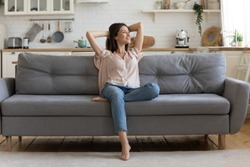 In cozy living room happy woman put hands behind head sitting leaned on couch 30s european female enjoy lazy weekend or vacation, housewife relaxing feels satisfied accomplish chores housework concept