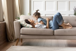 In cozy living room on comfy couch lying mother and her little cheery daughter. Kid girl lay on mom enjoy playtime and positive communication. Funny time together at home, love and protection concept