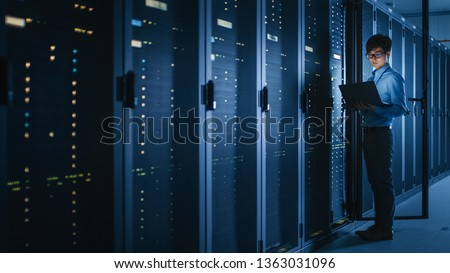 In Dark Data Center: Male IT Specialist Stands Beside the Row of Operational Server Racks, Uses Laptop for Maintenance. Concept for Cloud Computing, Artificial Intelligence, Cybersecurity.