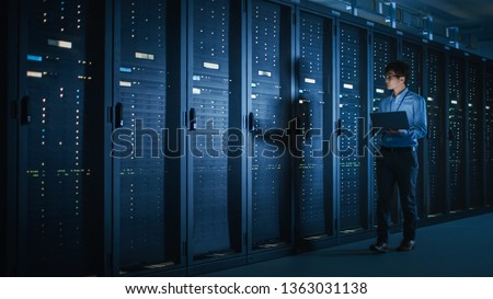 In Dark Data Center: Male IT Specialist Walks along the Row of Operational Server Racks, Uses Laptop for Maintenance. Concept for Cloud Computing, Artificial Intelligence, Supercomputer, Cybersecurity