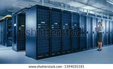 In Data Center: Female IT Specialist Walks along the Row of Operational Server Racks, Uses Laptop to Run Maintenance Programme. Modern High-Tech Telecommunications Operational Data Center.