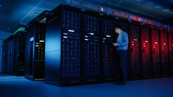 In Data Center: Male IT Specialist Walks along the Row of Operational Server Racks, Uses Laptop for Maintenance. Concept for Telecommunications, Cloud Computing, Artificial Intelligence, Supercomputer
