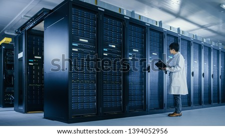 In Data Center: Male IT Specialist Wearing White Coat Stands Beside Server Rack, Uses Laptop Computer to Run Maintenance Diagnostics Tools, Controls so that Database Works at Optimal Level.