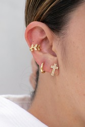 In ear are three earrings. One is a small cross with zircons, the second is a hoop and the last is a gold ear cuff.