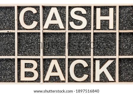 In einen Sammelkasten mit schwarzen Deko-Sand geordnete Sperrholz-Buchstaben die Wörter CASH BACK darstellend in Draufsicht auf weißen Hintergrund. Stok fotoğraf ©