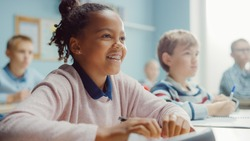 In Elementary School Class: Portrait of a Brilliant Black Girl with Braces Smiles, Writes in Exercise Notebook. Junior Classroom with Diverse Group of Children Learning New Stuff