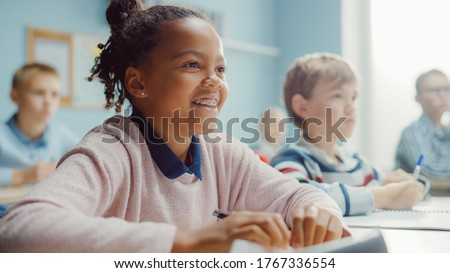 In Elementary School Class: Portrait of a Brilliant Black Girl with Braces Smiles, Writes in Exercise Notebook. Junior Classroom with Diverse Group of Children Learning New Stuff Stock photo ©