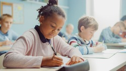 In Elementary School Class: Portrait of a Brilliant Black Girl with Braces Writes in Exercise Notebook, Smiles. Junior Classroom with Diverse Group of Children Learning New Stuff