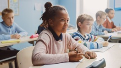 In Elementary School Classroom Brilliant Black Girl Writes in Exercise Notebook, Taking Test and Writing Exam. Junior Classroom with Diverse Group of Children Working Diligently and Learning New Stuff