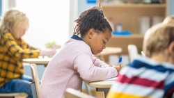 In Elementary School Classroom Brilliant Black Girl Writes in Exercise Notebook, Taking Test and Writing Exam. Junior Classroom with Group of Bright Children Working Diligently and Learning New Stuff