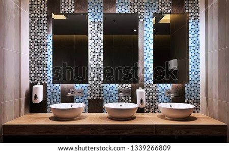 In front of the hand wash bar with mirror glass and wash basins in a restroom