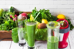 In front of the wall, green fruits and vegetables and a healthy drink blended were prepared. The process of preparing green smoothiein a kitchen blender.