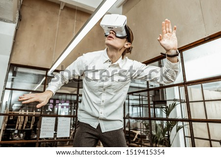 In frustration. Serious office worker standing in the middle of the office and enjoying modern technologies