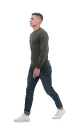 in full growth. a confident man in jeans walks forward .