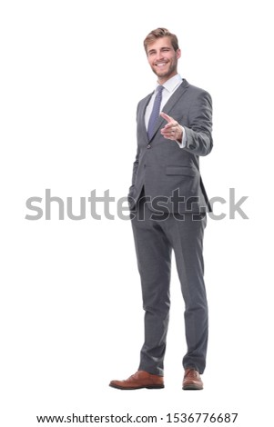 in full growth. smiling businessman holding out his hand for a handshake.