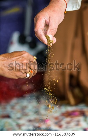 In Haldi ceremony, which is celebrated the day before the indian wedding ceremony, two hands is sprinlking turmeric powder