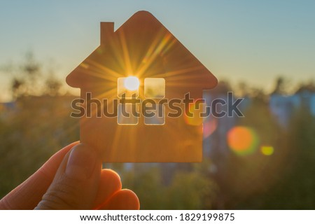 in hand a close-up of a small sketchy wooden house, through the window of which the sun's rays of the setting or rising sun are visible. The idea is to find your own home, hoping for a new day.