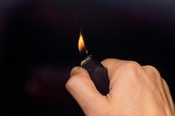 in hand a lit lighter on a dark background