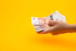 In hand a pack of five thousandth Russian rubles, yellow background