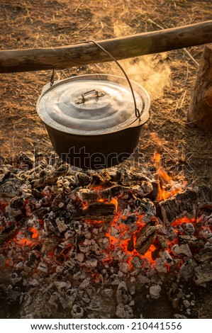 In hanging on a log cast iron cauldron on hot embers fading campfire stew boiling potatoes. Heated smoke rises in warm rays of evening sunset. Close-up view with space for text on blurred background