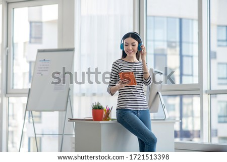 In headphones. Dark-haired woman in headphones holding a tablet