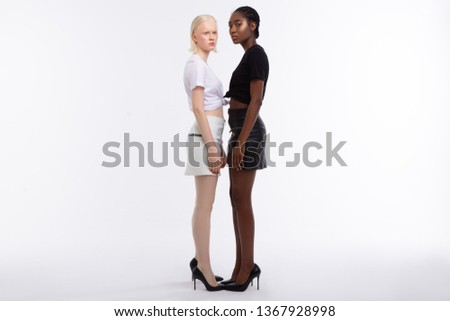 In high-heeled shoes. Models with different skin color wearing black leather high-heeled shoes #1367928998