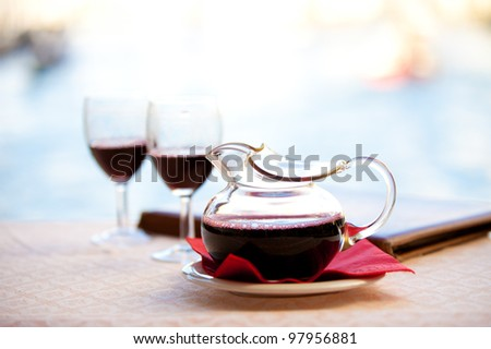 In Italy a Carafe a red wine - Chianti sits after being poured into glasses by the water under Rialto Bridge