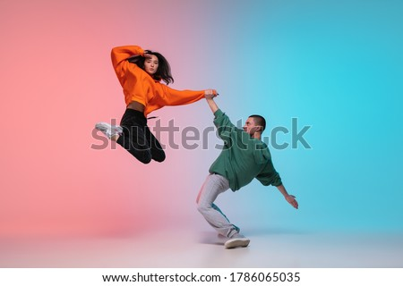 In jump. Boy and girl dancing hip-hop in stylish clothes on colorful gradient background at dance hall in neon. Youth culture, movement, style and fashion, action. Fashionable portrait. Street dance.