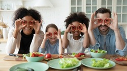 In kitchen couple and multi racial daughters prepare vegetable salad having fun make funny faces cover eyes with red paprika circles looking like eyewear, binoculars shape, cookery, family joy concept