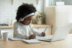 In kitchen schoolgirl do homework, focused little African girl wear headphones watch video lesson using laptop app, interested in on-line web virtual class studying from at home, homeschooling concept
