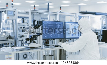 In Laboratory Over the Shoulder View of Scientist in Protective Clothes Doing Research on a Personal Computer. Modern Manufactory Producing Semiconductors and Pharmaceutical Items.