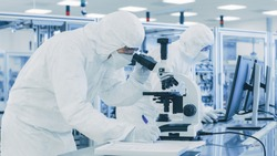 In Laboratory Scientist in Protective Clothes Doing Research, Using Microscope and Writing Down Data. Workers Working on a Modern Manufactory Producing Semiconductors and Pharmaceutical Items.