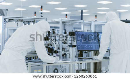 In Laboratory Scientists in Protective Clothes Doing Research, Using Microscope and Entering Data into Personal Computer. Modern Manufactory Producing Semiconductors and Pharmaceutical Items.