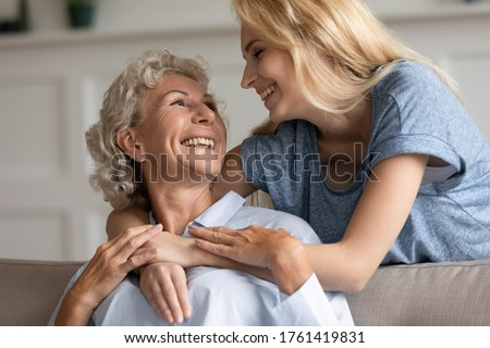 In living room elderly mom sit on sofa while adult grown up daughter hugs her from behind relatives women looking at each other with warmth love close up. Family bond, Mother Day celebration, concept