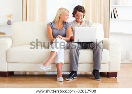 In love couple using a laptop while sitting on a sofa