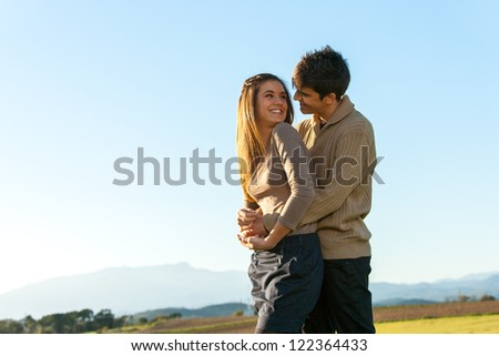 In love teen couple showing affection outdoors.