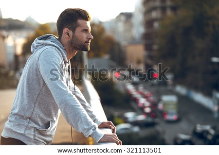 In love with his city. Side view of pensive young man in headphones looking away while standing on the bridge #321113501