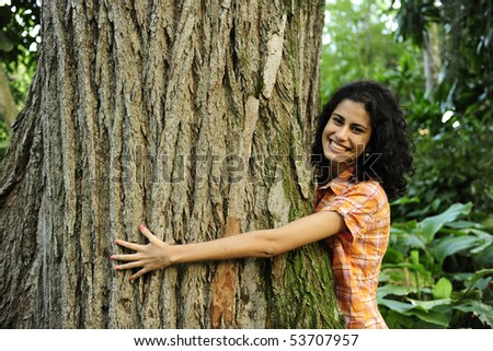 In love with nature: happy woman hugging a tree in the forest