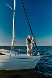 In love with the sea. Full length of beautiful senior couple standing on the side of sail boat or yacht deck floating in the calm blue sea, hugging and enjoying amazing sunset