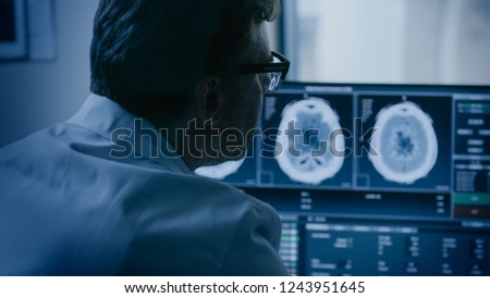 In Medical Laboratory Patient Undergoes MRI or CT Scan Process under Supervision of Radiologist in Control Room, He Watches Procedure and Monitors Brain Activity Results.