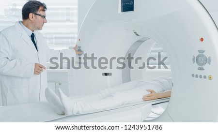 In Medical Laboratory Radiologist Controls MRI or CT or PET Scan with Female Patient Undergoing Procedure. High-Tech Modern Medical Equipment. Friendly Doctor Chats with Patient.