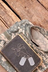 In memory of a brave soldier. Military camouflage clothes, old book, and dog tags on wood.