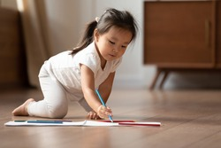 In modern cozy light living-room on warm floor little preschool asian girl holding pencil, drawing pictures on album at home. Pastime and good hobby, development of creativity and skill in kid concept