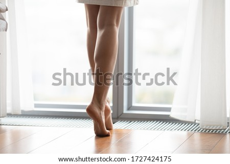 In morning woke up woman open curtain stands tiptoes barefoot feet looks out the window close up. In-floor heating system convector built into floor. Repair renovation. Comfort climate at home concept
