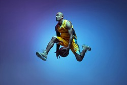 In motion. Portrait of athletic african-american male basketball player training isolated in neon light on blue background. Concept of health, professional sport, hobby. Passionate, fashionable