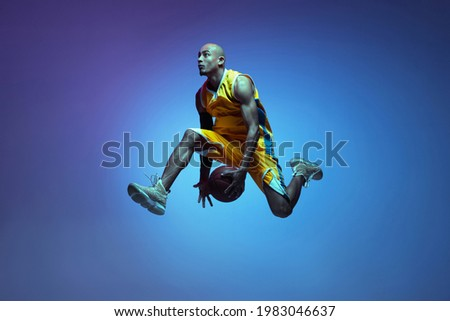 In motion. Portrait of athletic african-american male basketball player training isolated in neon light on blue background. Concept of health, professional sport, hobby. Passionate, fashionable ストックフォト ©