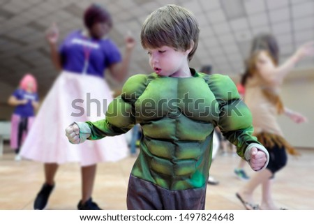 In motion subject preschool age boy enjoying indoors activities wearing a green puffy six-pack muscular costume against an indoor bokeh playground with toys and other children playing around